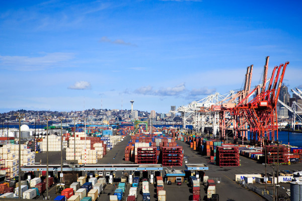 A photo taken from a bridge heading to West Seattle showing al he infastructure of cranes and shipping containers in he port of Seattle.